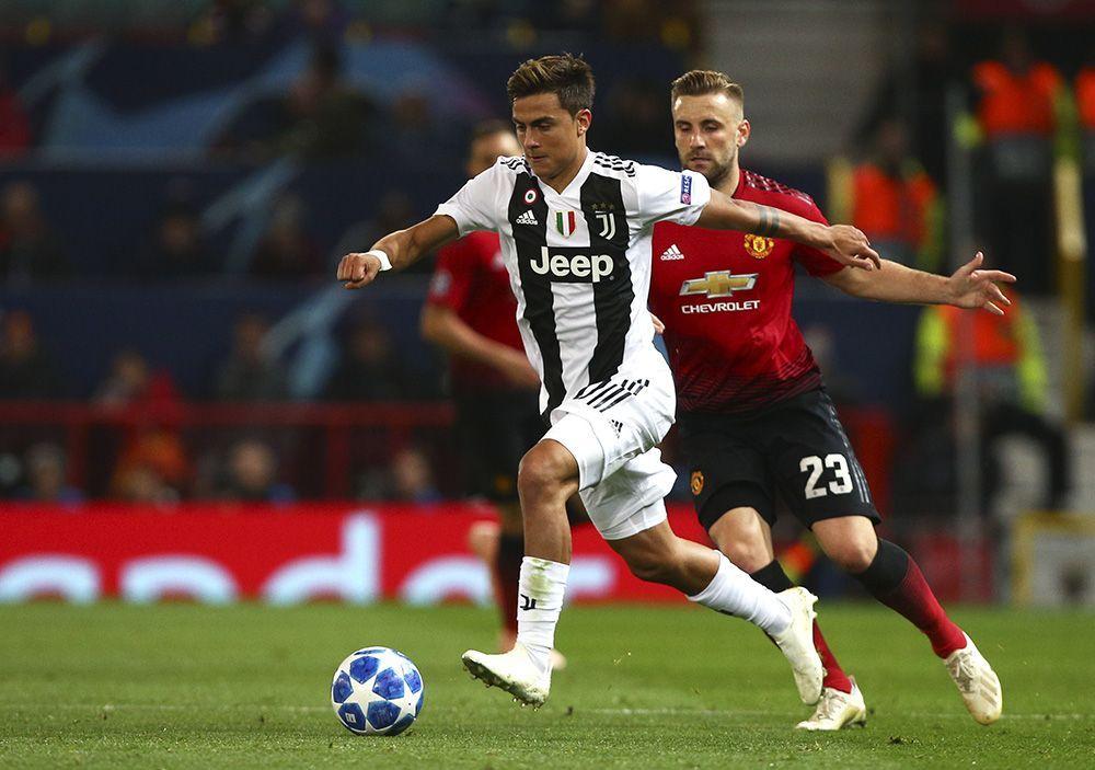 El delantero de la Juventus, el argentino Paulo Dybala, escapa con el balón ante la marcación del defensa del Manchester United, Luke Shaw (23), durante el partido del Grupo H de la Liga de Campeones en el estadio Old Trafford, en Manchester, Inglaterra, el martes 23 de octubre de 2018. (AP Foto/Dave Thompson)