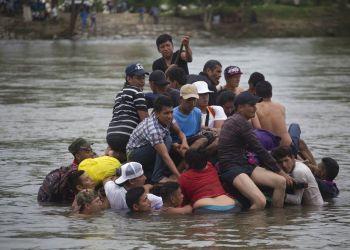 Un grupo de migrantes centroamericanos cruzan el río Suchiate en una balsa hecha de llantas de tractor y tablas, en la frontera entre Guatemala y México, en Ciudad Hidalgo, México, 20 de octubre de 2018. Foto: Moises Castillo / AP.