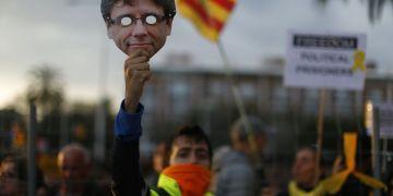 Un manifestante partidario de la independencia de Cataluña sostiene una máscara del exlíder catalán Carles Puigdemont durante una protesta en Barcelona, España, el domingo 25 de marzo de 2018. Foto: Manu Fernández / AP.