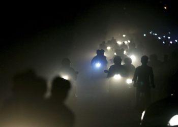 Motociclistas indios atraviesan una espesa nube de smog y polvo en las afueras de Nueva Delhi. Foto: Altaf Qadri / AP.