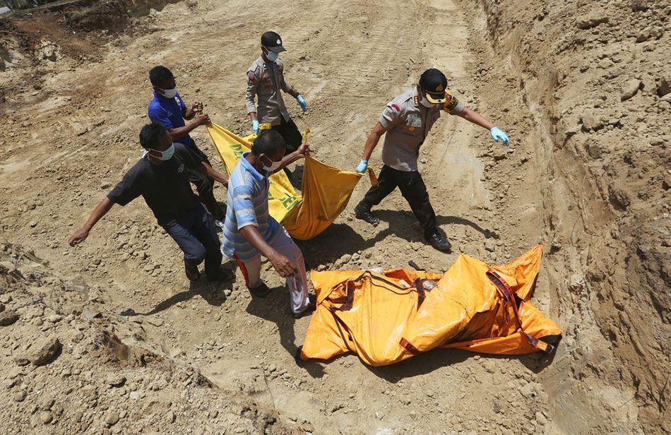 Socorristas indonesios cargan el cadáver de una víctima de un terremoto y tsunami hacia una fosa común en Palu, Indonesia, el lunes 1 de octubre de 2018. Foto: Tatan Syuflana / AP.