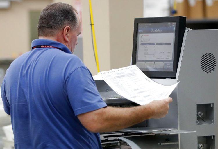 Un empleado de la oficina del Supervisor de Elecciones del condado de Broward pasa boletas por una máquina mientras cuenta votos de la elección legislativa del jueves 8 de noviembre de 2018 en Lauderhill, Florida. (AP Foto/Wilfredo Lee)