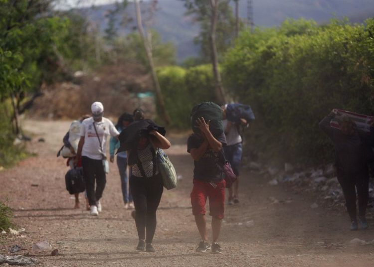 """En esta imagen, tomada el 31 de agosto de 2018, venezolanos cruzan ilegalmente la frontera con Colombia, a Villa del Rosario, por una ruta conocida como """"trocha"""". Algunos venezolanos no pueden cruzar por un paso fronterizo oficial porque carecen de documentación oficial, como pasaporte, y emplean carreteras de tierra ilegales gestionadas por hombres armados y vestidos de uniforme. (AP Foto/Ariana Cubillos)"""