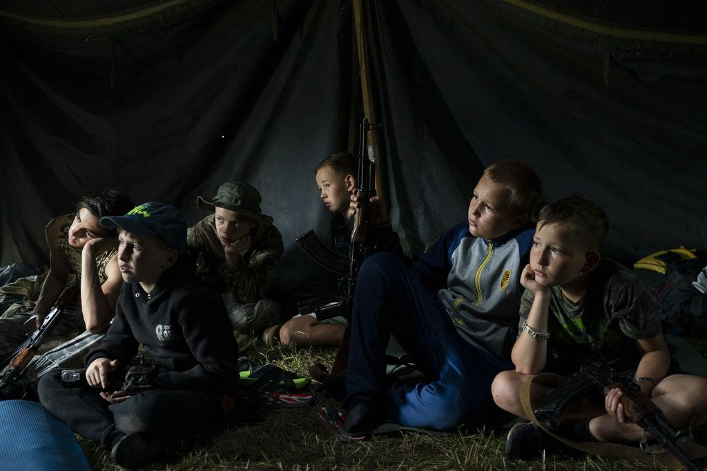 Niños que participan en un campamento de elementos nacionalistas de Ucrania con sus fusiles a su lado escuchan a un instructor el 28 de julio de 2018. En los campamentos les inculcan una ideología nacionalista y les enseñan a combatir a los rusos y sus partidarios. Foto: Felipe Dana / AP.