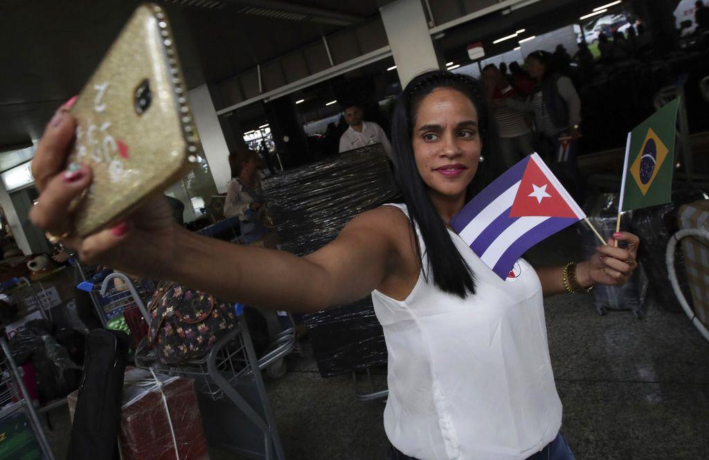Una doctora cubana sosteniendo banderas de Cuba y Brasil se toma una selfie antes de que ella y otros médicos de su país regresen a casa desde el aeropuerto de Brasilia, Brasil, el jueves 22 de noviembre de 2018. Foto: Eraldo Peres / AP.
