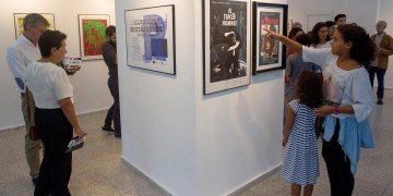 """Personas observan los carteles de la exposición """"Clásicos restaurados del cine europeo"""", en la galería 23 y 12 este 8 de diciembre en La Habana Foto: Yander Zamora / EFE."""