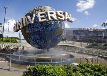 Visitantes de un parque temático descansado con rocío de agua en el globo en Universal Studios City Walk en Orlando, Florida. Foto: John Raoux / AP.