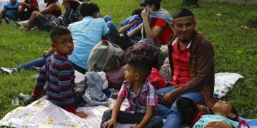 Freddy Rivas (segundo por la derecha), natural de Tocoa, Honduras, sus hijos Josué (izquierda) y Elkin (centro) y su hermano Mario esperan la llegada de más migrantes a una caravana que viajará hacia la frontera de Estados Unidos, en San Pedro Sula, Honduras, el 14 de enero de 2019. (AP Foto/Delmer Martinez)