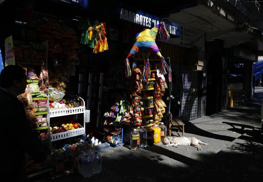 Un perro acostado frente a una tienda con piñatas en la colonia Roma Sur de la Ciudad de México.(Foto AP/Rebecca Blackwell)