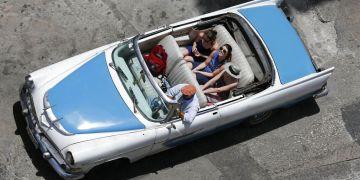 En esta imagen tomada el 13 de mayo de 2015, turistas pasean en un auto clásico descapotable por La Habana. Foto: Desmond Boylan / AP.