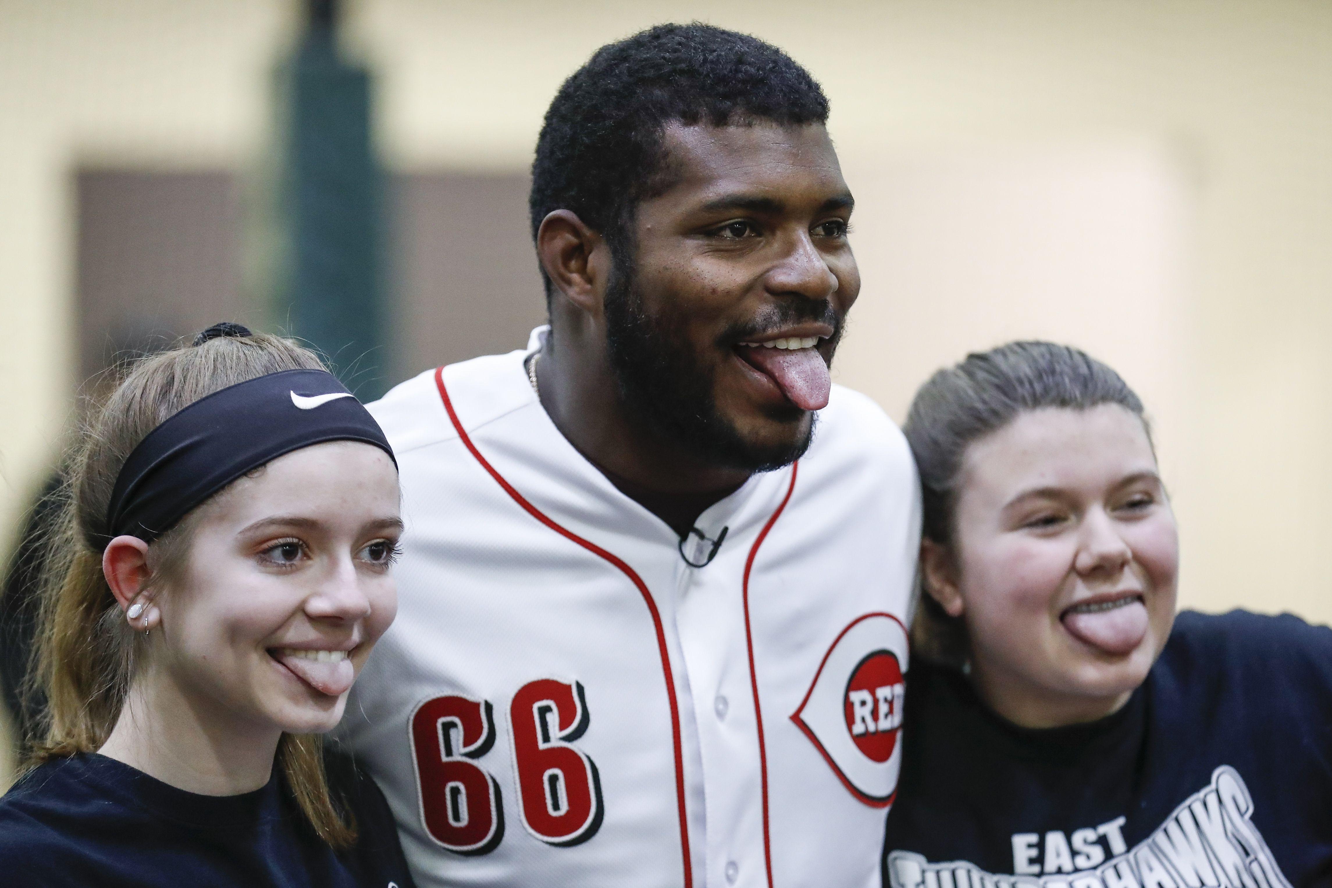 Yasiel Puig de los Rojos de Cincinnati posa para fotos con dos deportistas durante una presentación de la academia juvenil de los Rojos, el miércoles 30 de enero de 2019. (AP Foto/John Minchillo)