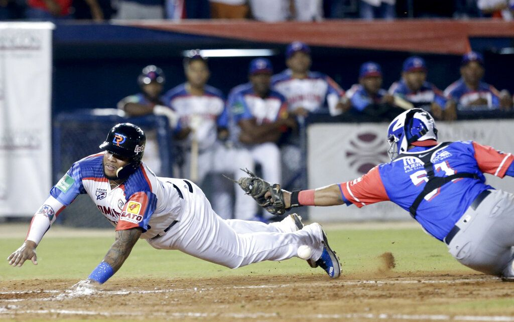 Edwin Espinal, de las Estrellas Orientales de República Dominicana, se desliza a salvo en el plato en la parte baja de la cuarta entrada en partido contra los Cangrejeros de Santurce de Puerto Rico en la Serie del Caribe en el estadio Rod Carew en Ciudad de Panamá, el jueves 7 de febrero de 2019. (AP Foto/Arnulfo Franco)
