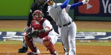 ARCHIVO - En esta foto del 24 de octubre de 2018, Manny Machado de los Dodgers de Los Ángeles Dodgers batea un sencillo frente al receptor Christian Vázquez de los Medias Rojas en el segundo juego de la Serie Mundial en Boston. (AP Foto/Elise Amendola, archivo)