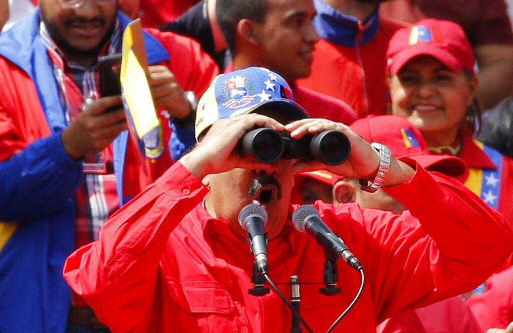 El presidente Nicolás Maduro ve a través de unos binoculares durante un acto en Caracas, Venezuela, el sábado 2 de febrero de 2019. Foto: Ariana Cubillos / AP.