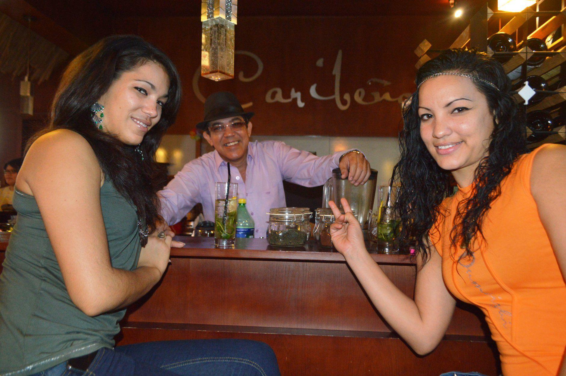 Miguel Nicolau, cuando se desempeñaba como barman del restaurante Caribeño, junto a dos bailarinas cubanas.