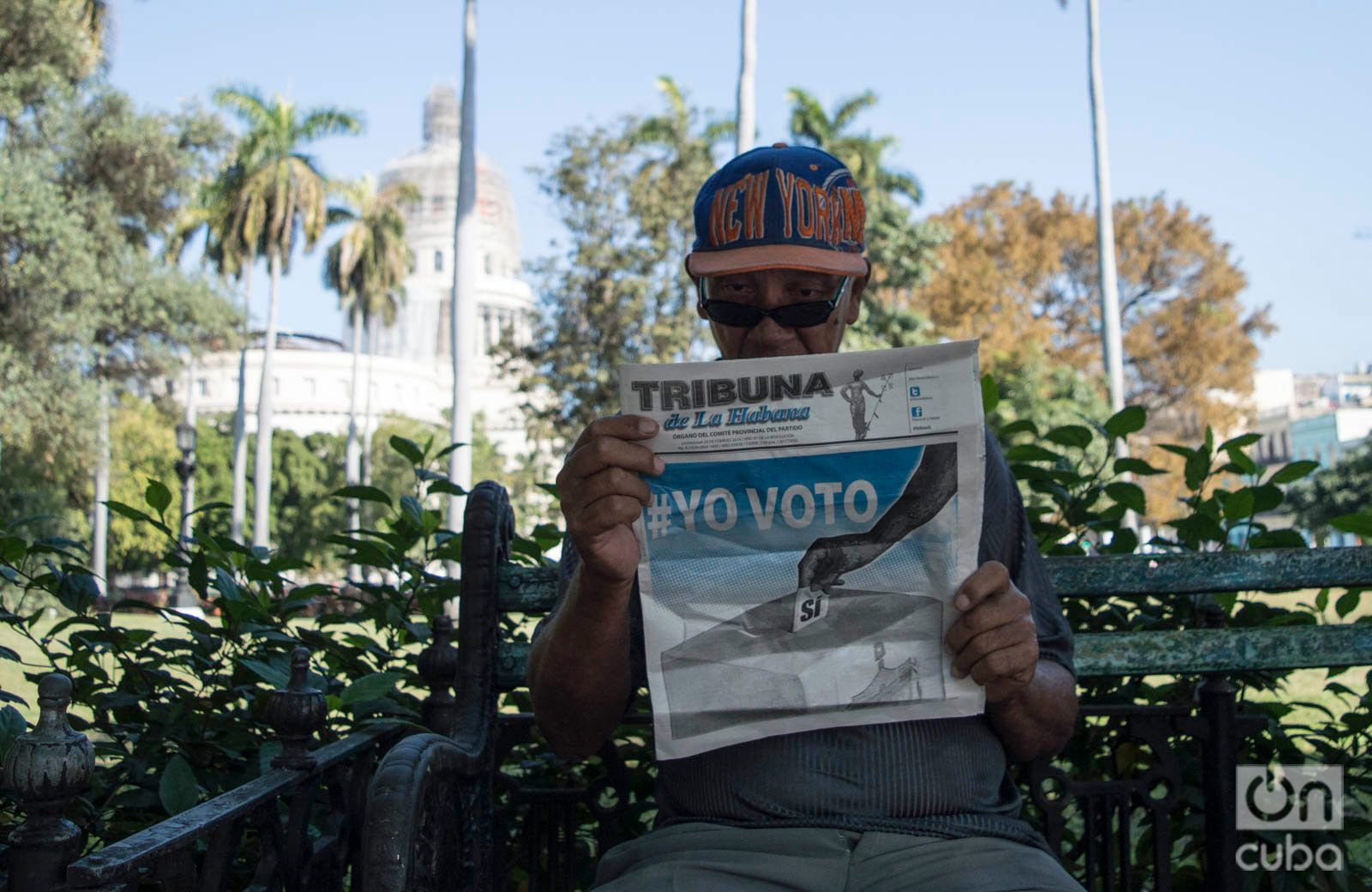 """Un hombre lee un periódico en La Habana con propaganda a favor del voto por el """"sí"""" en el referendo constitucional de Cuba, el 24 de febrero de 2019. Foto: Otmaro Rodríguez."""