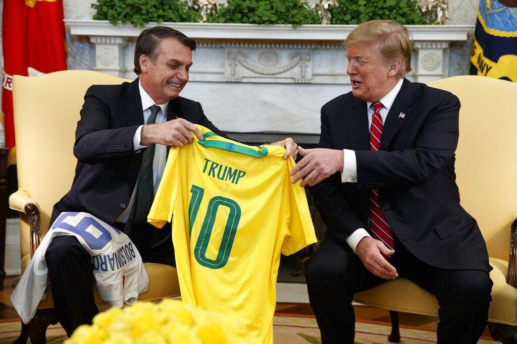 El presidente brasileño, Jair Bolsonaro, entrega al presidente Donald Trump una camiseta de fútbol de la selección nacional brasileña en la Oficina Oval de la Casa Blanca, el martes 19 de marzo de 2019, en Washington, D.C. Foto: Evan Vucci / AP.