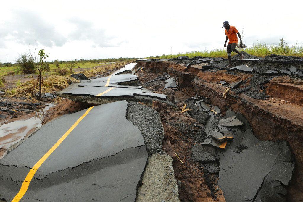 Un hombre cruza por una parte de una carretera dañada por el paso del ciclón Idai en Nhamatanda, Mozambique, aproximadamente a 50 kilómetros (30 millas) de Beira, el viernes 22 de marzo de 2019. (AP Foto/Tsvangirayi Mukwazhi)
