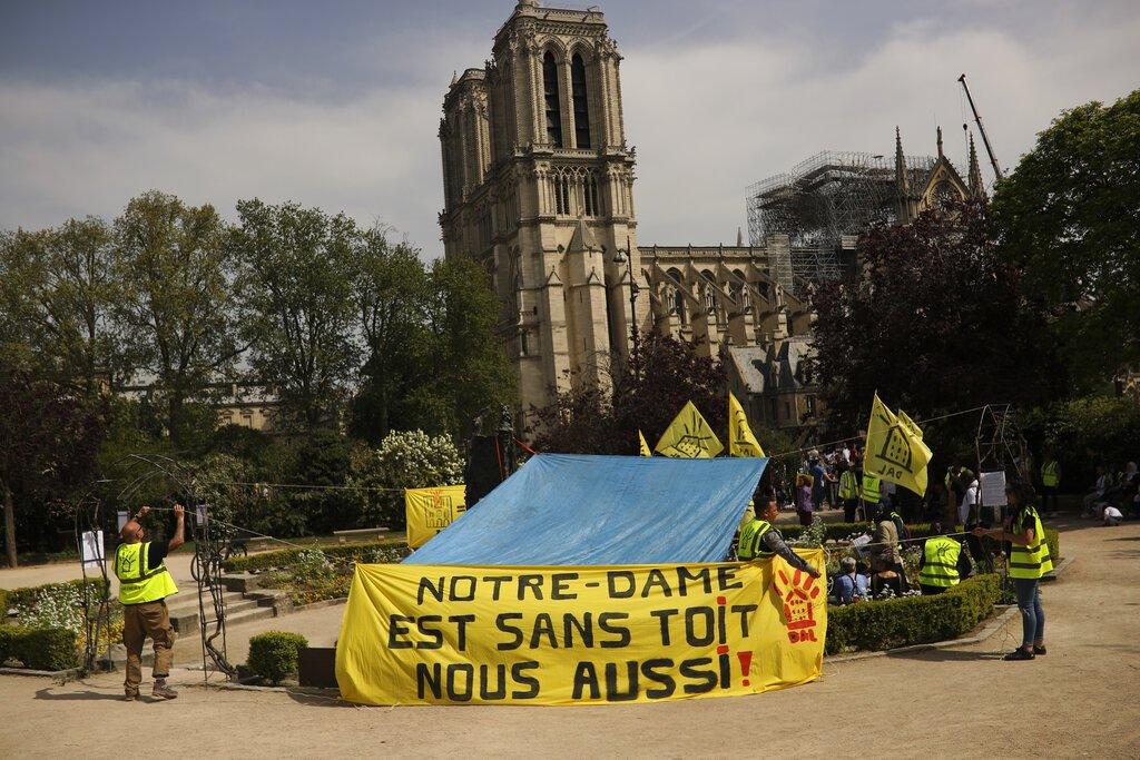 Defensores de la vivienda pública protestan frente a la destruida catedral de Notre Dame para exigir que se recuerde a los más pobres de Francia, en París, el lunes 22 de abril de 2019. Foto: Francisco Seco / AP.