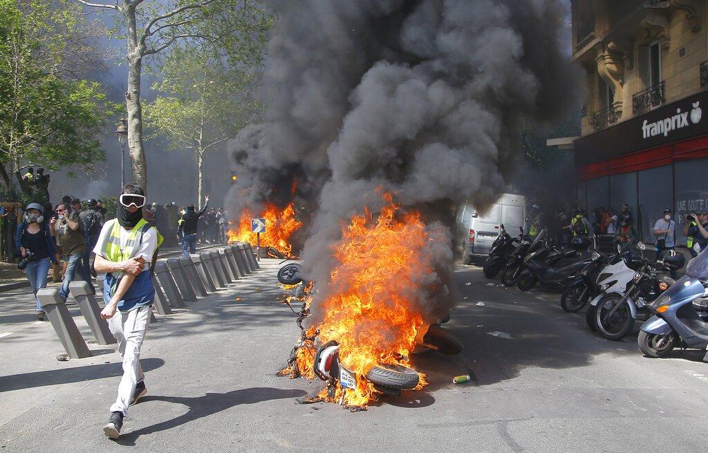 Un hombre corre junto a una motocicleta en llamas durante una protesta de chalecos amarillos en París, el sábado 20 de abril de 2019. Foto: Michel Euler/AP.