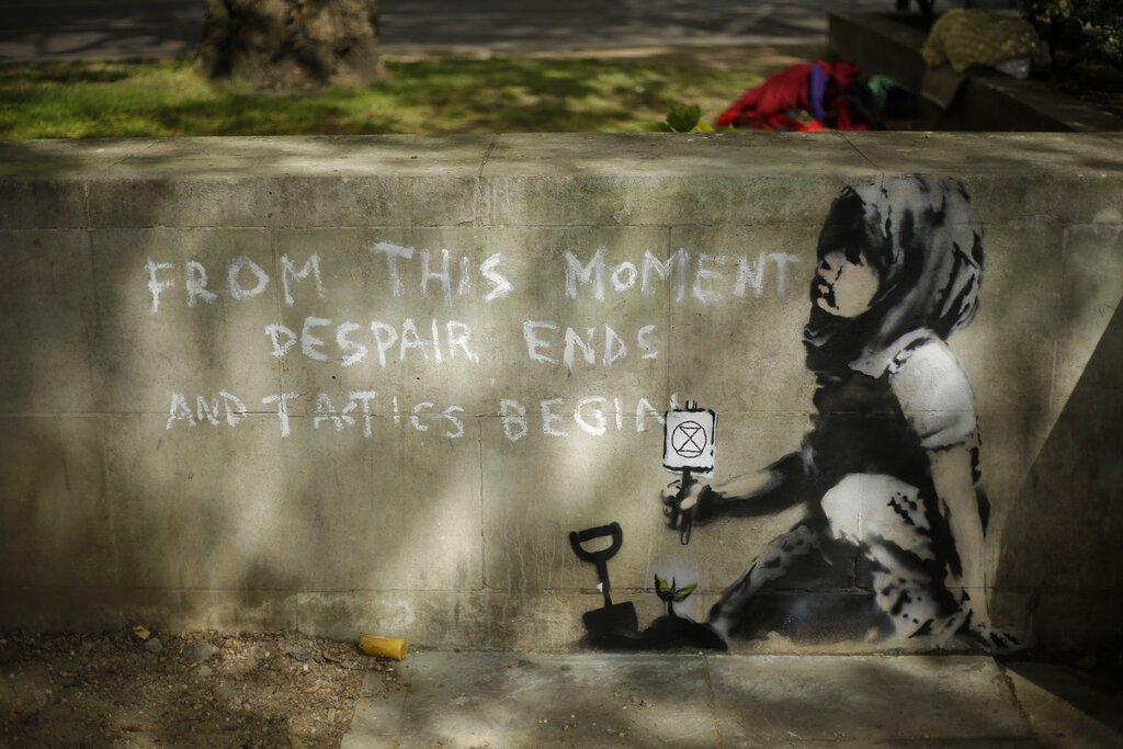 La sombra de un árbol sobre un mural que se sospecha podría ser de Banksy en una pared donde se había colocado el campamento de los manifestantes del grupo. Foto:Matt Dunham/ AP.