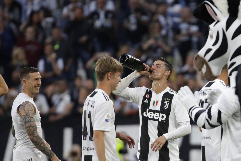 Cristiano Ronaldo (derecha) de Juventus festeja la obtención del título de la Serie A tras vencer 2-1 a la Fiorentina, el sábado 20 de abril de 2019. (AP Foto/Luca Bruno)