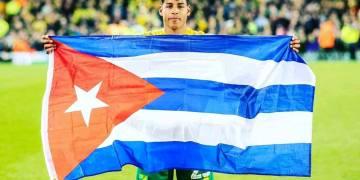 Onel Hernández con la bandera cubana, tras el ascenso del Norwich City a la Premier League inglesa. Foto: Perfil del Facebook del futbolista.