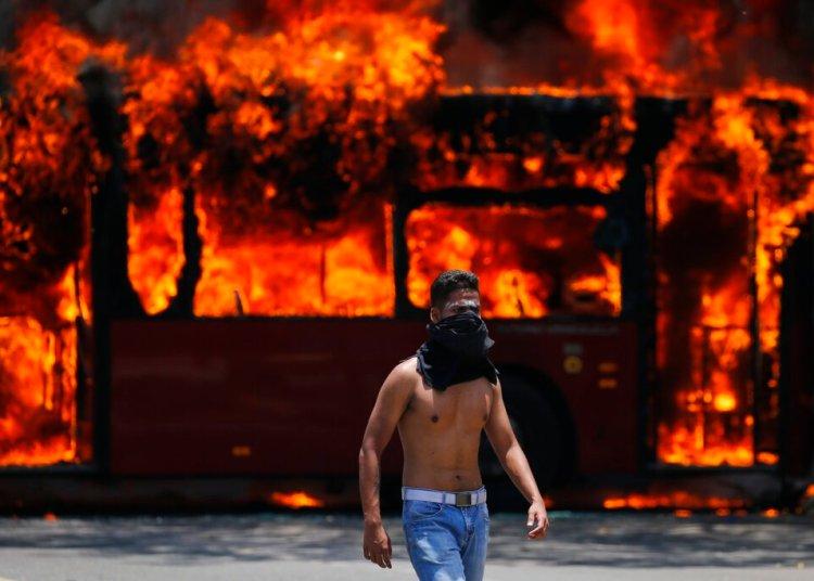 Un manifestante antigubernamental camina cerca de un autobús que fue incendiado por opositores al presidente de Venezuela, Nicolás Maduro, en Caracas, el martes 30 de abril de 2019.  Foto:  Fernando Llano / AP.