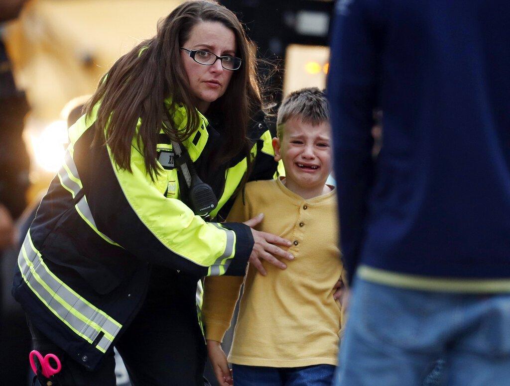 Una funcionaria guía a un alumno desde un autobús a un centro recreativo para ser reunido con sus padres después de un tiroteo en una escuela secundaria en los suburbios de Denver, el martes 7 de mayo de 2019, en Highlands Ranch, Colorado. Foto: David Zalubowski / AP.