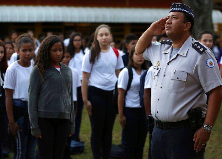 En esta imagen tomada el 28 de marzo de 2019, el mayor Edney Freire hace un saludo militar durante la ceremonia de la bandera en el patio principal de la escuela estatal número 7 de Ceilandia, en Brasilia, Brasil. Foto: Eraldo Peres / AP.