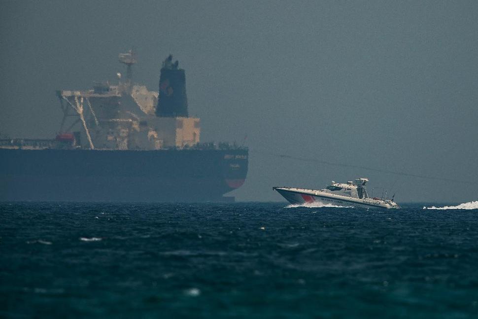 Un buque de la guardia costera emiratí pasa cerca de un petrolero frente a la costa de Fujairah, Emiratos Árabes Unidos, el lunes 13 de mayo de 2019. Foto Jon Gambrell/AP.
