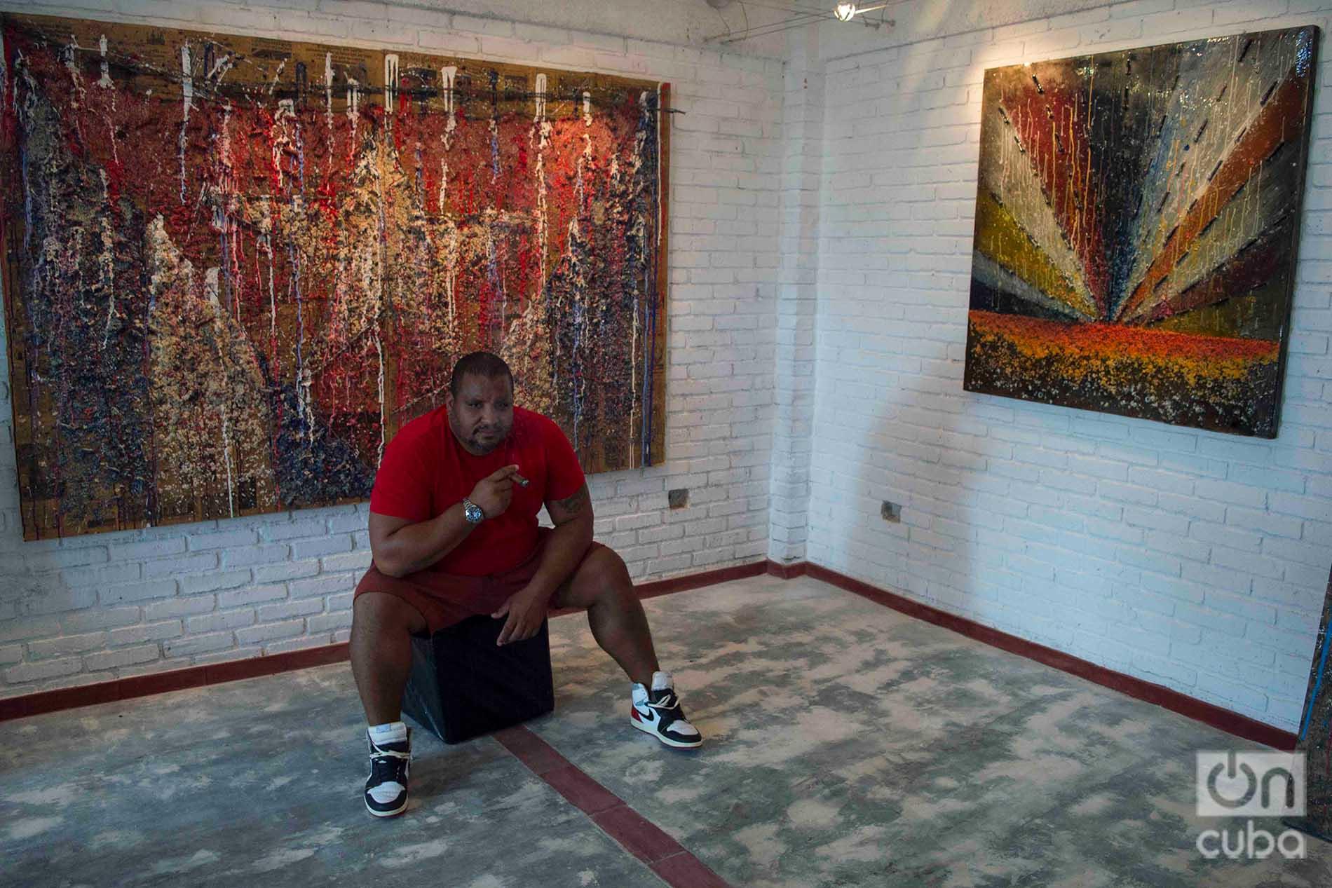 El artista cubano Michel Mirabal junto a obras de la exposición personal que exhibe en su galería taller, como parte de las actividades colaterales de la XIII Bienal de La Habana. Foto: Otmaro Rodríguez.