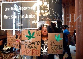 Pilar DeJesus, junto con una coalición de manifestantes, sostiene un letrero exhortando a los legisladores a aprobar la posesión de marihuana contra las puertas del Senado en el Capitolio estatal el miércoles 19 de junio de 2019 en Albany, Nueva York. Foto: Hans Pennink / AP.