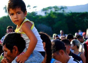 Un venezolano con un niño sobre los hombros espera para cruzar el puente internacional Simón Bolívar a Cúcuta, Colombia, sábado 8 de junio de 2019. Foto: Ferley Ospina / AP.