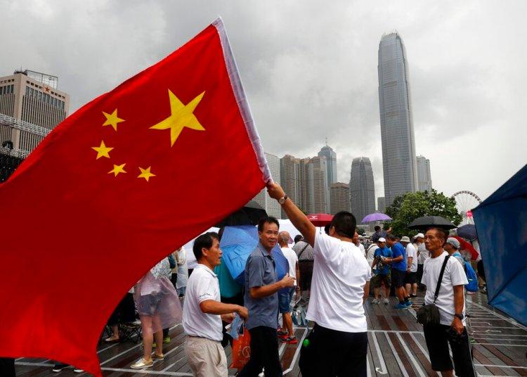 Un simpatizante de China ondea una bandera nacional china durante una contramanifestación en apoyo de la policía en Hong Kong el sábado 20 de julio de 2019. Foto: Vincent Yu/ AP.