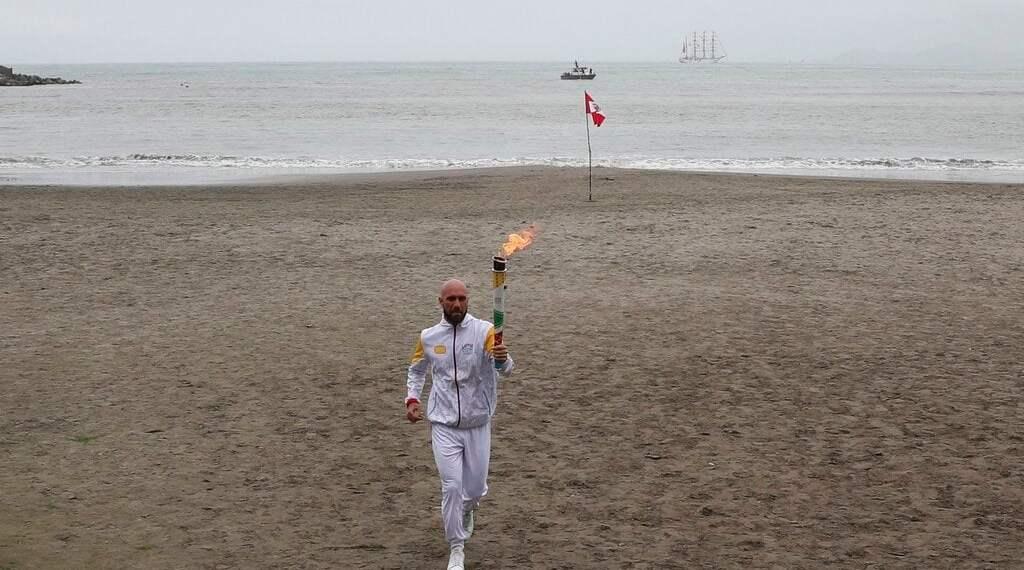 El extenista peruano Luis Horna corre con la antorcha de los Juegos Panamericanos en la playa Los Yuyos de Lima, el viernes 26 dejulio de 2019, horas antes de la ceremonia inaugural (AP Foto/Martín Mejía)