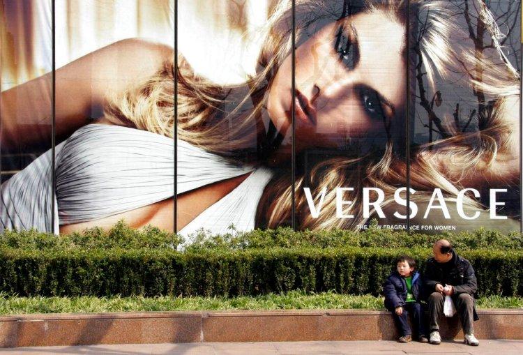 Fotografía de archivo del 15 de febrero de 2008 de un niño y un hombre sentados frente a una publicidad de Versace en Shanghái, China. (AP Foto/Eugene Hoshiko, Archivo)