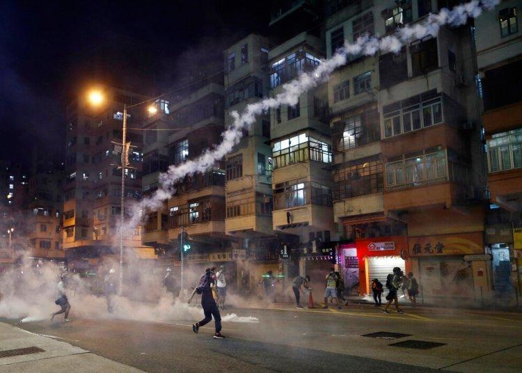 Unos manifestantes caminan en medio de gases lacrimógenos lanzados por la policía en Hong Kong el miércoles 14 de agosto del 2019. Foto: Vincent Yu / AP.