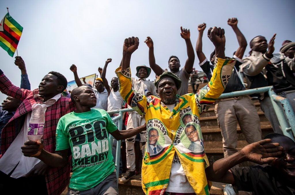 Varias personas, una de ellas con una chaqueta con la cara del expresidente Robert Mugabe, cantan mientras esperan para ver el cuerpo del exmandatario en el estadio Rufaro de Harare, Zimbabue. Foto: Ben Curtis / AP.