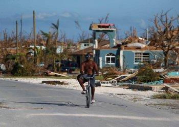 Un hombre pasea en bicicleta entre los escombros provocados por el paso del huracán Dorian, en Marsh Harbor, en la isla de Ábaco, Bahamas, el 6 de septiembre de 2019. (AP Foto/Fernando Llano)