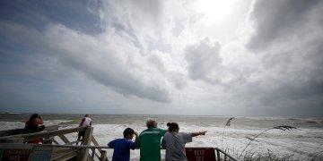 Unas personas observan la marea alta del océano Atlántico previo al posible paso del huracán Dorian, en Vero Beach, Florida, el lunes 2 de septiembre de 2019. (AP Foto/Gerald Herbert)