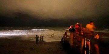 Varias personas caminan por el malecón mientras las bandas exteriores del huracán Dorian llegan a Vero Beach, Florida, la noche del lunes 2 de septiembre de 2019. (Foto AP/Gerald Herbert)