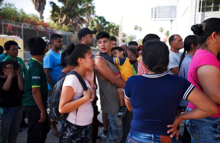 En esta fotografía de archivo del 1 de agosto de 2019, migrantes hacen fila en Matamoros, México, para recibir una comida donada por voluntarios estadounidenses, en el puente Puerto México que cruza hacia Brownsville, Texas. Foto: Emilio Espejel / AP / Archivo.