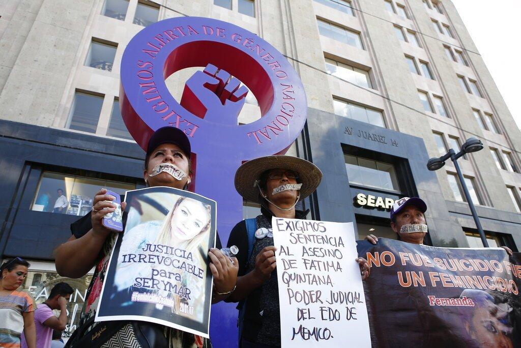 Sandra Soto, a la izquierda, sostiene una fotografía de su hermana asesinada, mientras que Lorena Gutierrez carga un letrero sobre su hija asesinada, al centro, frente a una estructura que exige atención a los feminicidios, en la Ciudad de México, el domingo 8 de septiembre de 2019. Foto: Ginnette Riquelme / AP.