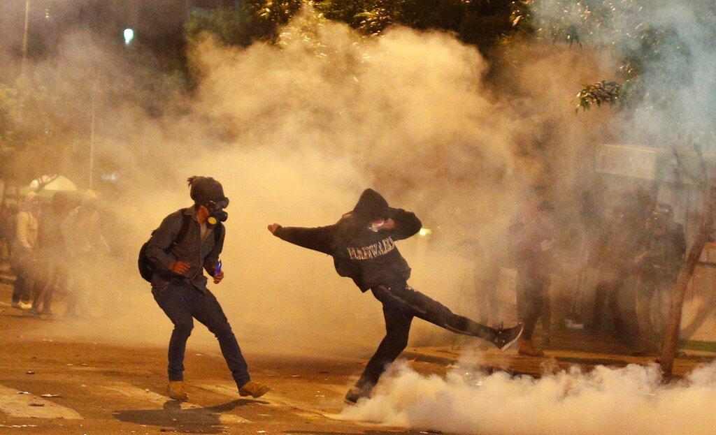Manifestantes envueltos en gases lacrimógenos lanzados por la policía protestan la reelección del presidente Evo Morales en La Paz, Bolivia, 23 de octubre de 2019. Foto: Juan Karita / AP.