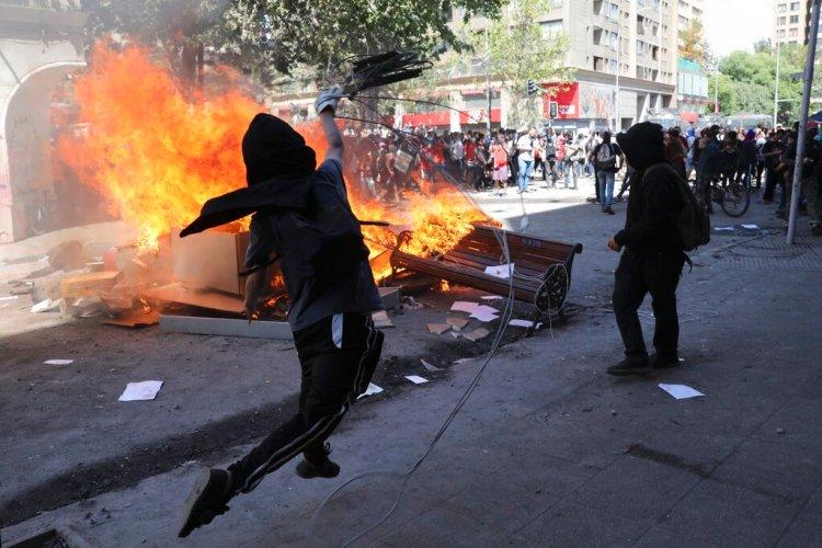 Un manifestante antigubernamental arroja un retrato del presidente Sebastián Piñera a una barricada en llamas en Santiago de Chile, durante las protestas de las últimas semanas en ese país sudamericano. Foto: Rodrigo Abd / AP / Archivo.