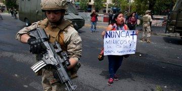 Una mujer protesta junto a un soldado en Santiago de Chile este sábado 19 de octubre. Foto: Esteban Felix/AP.