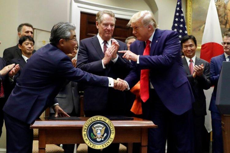 El presidente Donald Trump señala al embajador de Japón en Estados Unidos, Shinsuke Sugiyama, mientras el Representante Comercial de Estados Unidos, Robert Lighthizer, al centro, observa, el final de la ceremonia de una firma de acuerdo comercial con Japón en la Casa Blanca, el lunes 7 de octubre de 2019, en Washington. Foto: Evan Vucci / AP.