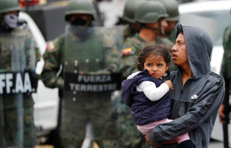 Un hombre que carga a una niña sale de un camino bloqueado durante las protestas contra el presidente Lenín Moreno, después de que soldados llegaran a reabrirlo en Quito, Ecuador, el lunes 7 de octubre de 2019. Foto: Dolores Ochoa / AP.