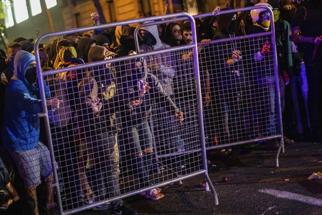 Manifestantes retiran una cerca ante la Delegación de Gobierno en Barcelona, España, el martes 15 de octubre de 2091. Foto: Bernat Armangue / AP.